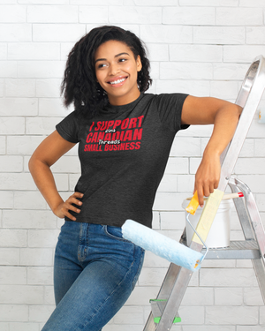 "An adult woman leaning against a ladder, holding a paint roller. She is wearing a charcoal grey heathered shirt that says ""I Support Canadian Small Business"" in red and ""Rink Threads"" in white, outlined in black. Rink Threads is superimposed over the red text."