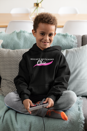 "A small boy playing video games,  wearing black hoodies that read ""Hockey Watching Chic"" in white with a pink brush stroke underneath."