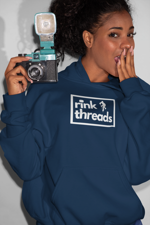 "An adult, holding a camera with her hand over her mouth. She is wearing a navy hoodie with the rink threads logo in the middle. The rink threads logo is a box with the words ""Rink Threads"" inside. The dot for the I is a puck and there is a hockey player on the right hand side of the logo."