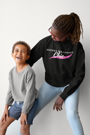"A woman and a small boy, laughing. She is  wearing black hoodies that read ""Hockey Watching Chic"" in white with a pink brush stroke underneath."
