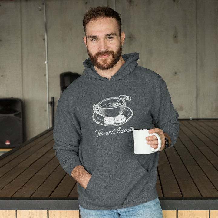 "An adult, smiling with a cup in his hand. He has one hand in the kangaroo pouf of a charchoal heathered hoodie with a sketch of a cup of tea in the middle. There si a hockey stick beign used as a stirrer and two pucks or ""Biscuits"" on the tea's plate. Beneath it in cursive is written ""Tea and Biscuits""."