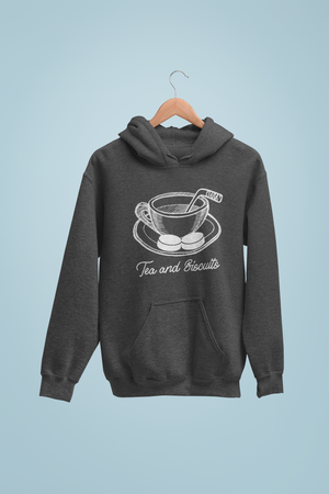 "A mockup of a charchoal heathered hoodie with a sketch of a cup of tea in the middle. There si a hockey stick beign used as a stirrer and two pucks or ""Biscuits"" on the tea's plate. Beneath it in cursive is written ""Tea and Biscuits"". It is on a hanger, against a light blue background."