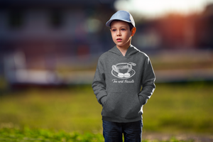 "A child in a field, wearing a charchoal heathered hoodie with a sketch of a cup of tea in the middle. There si a hockey stick beign used as a stirrer and two pucks or ""Biscuits"" on the tea's plate. Beneath it in cursive is written ""Tea and Biscuits""."
