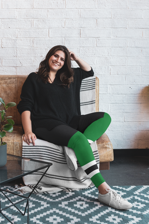 Woman lounging on the couch in a living room. She is wearing plus sized leggings. The leggings have a graphic that looks like she is wearing hockey pants and Green hockey socks with two white stripes and a black stripe between them.