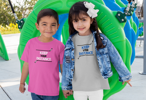 "Two kids holding hands at a playground. They are both wearing ""Keep Your Distance"" T-shirts. The one on the left is pink with White and black writing and the one on the right is sport grey with blue and black writing."