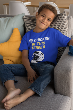 "A child sitting on the couch and smiling. He is wearing  a blue t-shirt that says ""No Chicken in this Tender"" in white and yellow. There is a graphic of a hockey goalie mask in white and black underneath the words."
