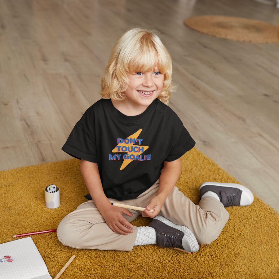 "Young child with blonde hair, sitting on the floor colouring,  wearing a black t-shirt that reads ""Don't Touch My Goalie"" in bold blue letters with a red shadow, in front of a yellow cartoon lightning bolt."