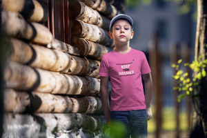"A child posing by a log cabin. He is wearing jeans and a pink t-shirt that says ""Keep your Distance"" in white and black. There is a hockey stick both above and below the words, framing them."