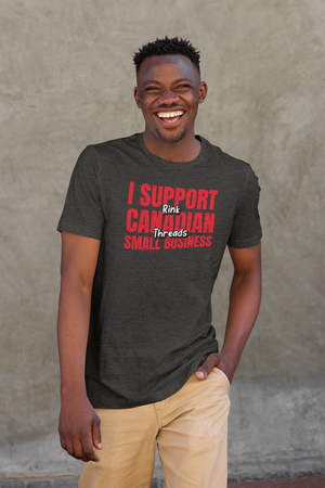 "An adult man smiling. He is wearing a charcoal grey heathered shirt that says ""I Support Canadian Small Business"" in red and ""Rink Threads"" in white, outlined in black. Rink Threads is superimposed over the red text."