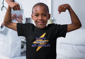 "Young boy flexing while wearing a black t-shirt that reads ""Don't Touch My Goalie"" in bold blue letters with a red shadow, in front of a yellow cartoon lightning bolt."