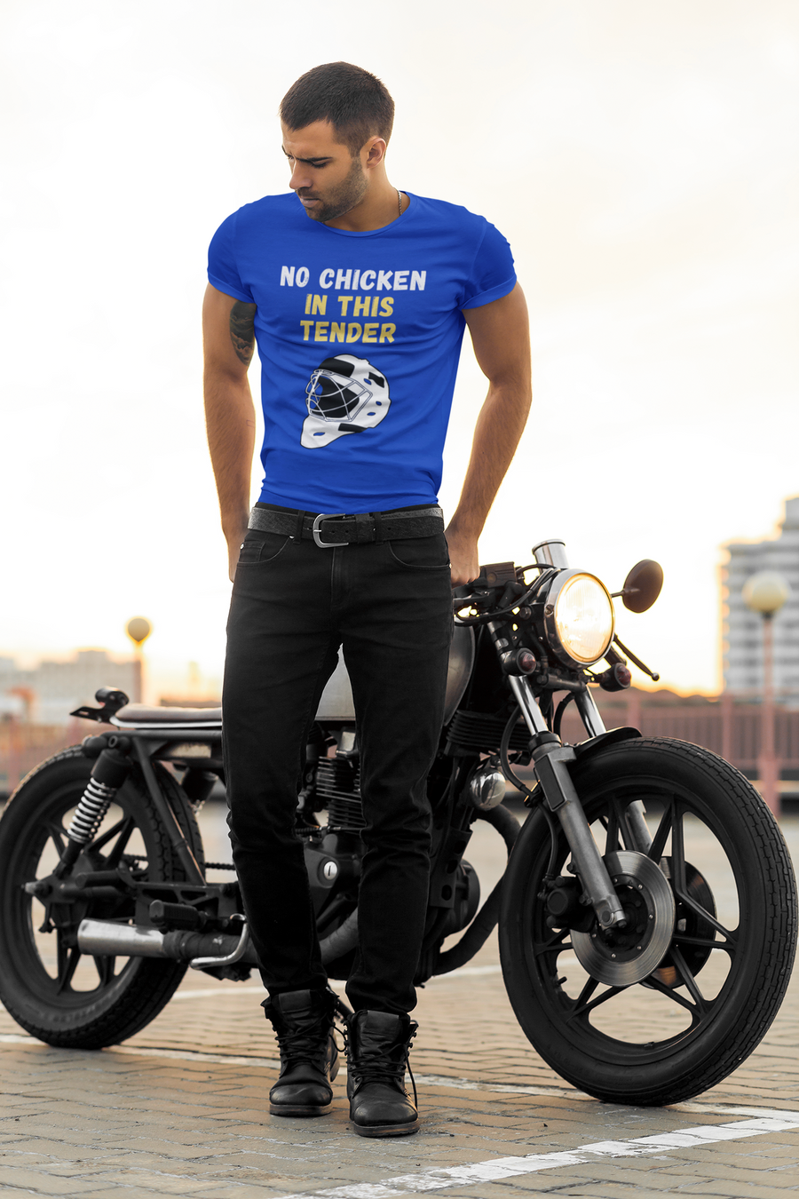 "An adult posing in front of a motorcycle. He is wearing  a blue t-shirt that says ""No Chicken in this Tender"" in white and yellow. There is a graphic of a hockey goalie mask in white and black underneath the words."