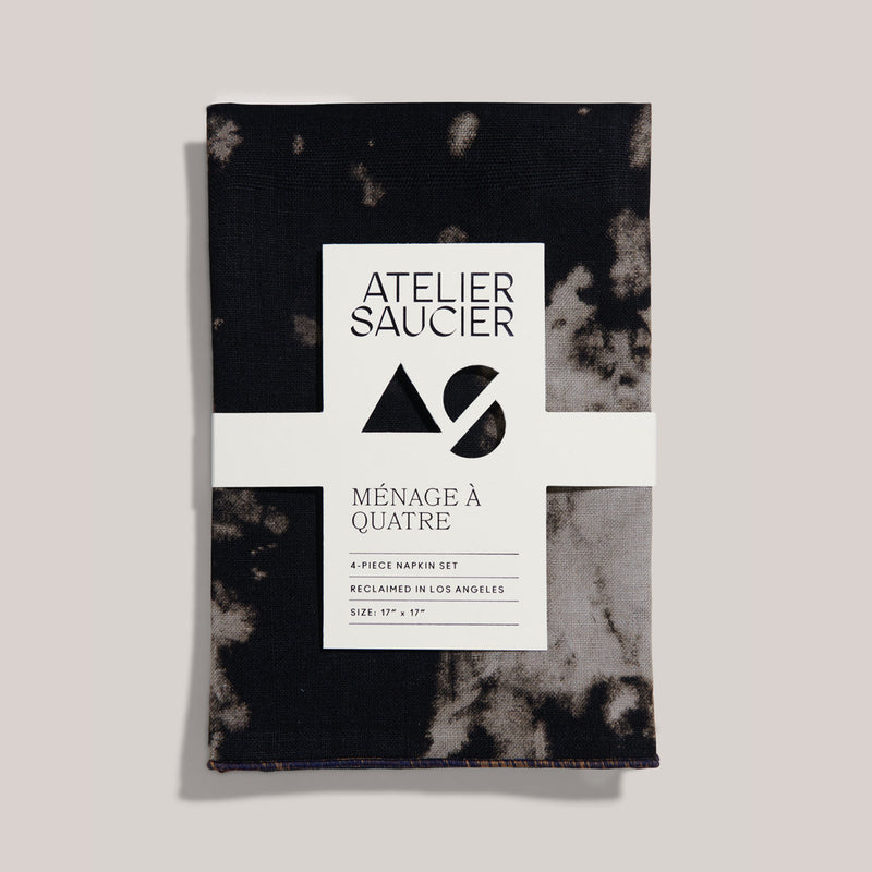 A 4-piece napkin set by Atelier Saucier sits alone in this frame. The napkins are 17 inches by 17 inches, are made from dead stock linen, and are dyed a dark black and grey tie dye. A paper card sits a top of this set featuring organic cut outs and the black and white Atelier Saucier logo.