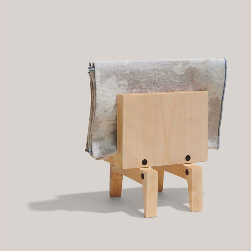 Here a birch Atelier Saucier napkin holder is shown from the front. A square holder is set on four legs--angular in shape and fits up to six napkins. In this specific frame, the holder has two sunrise Atelier Napkins.
