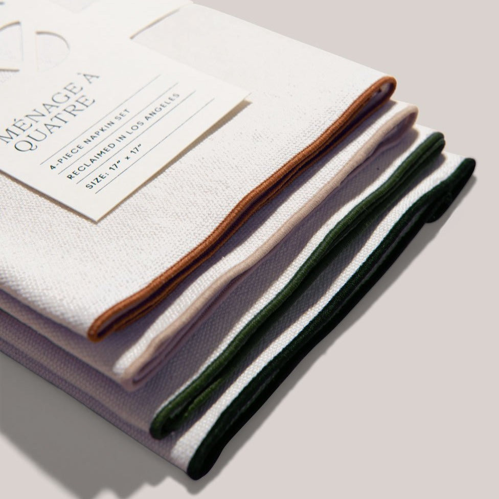A close up view of the mojave burlap napkin set's embroidered, rainbow finishes, including umber, sand, evergreen and navy. These are tucked neatly in place with the recyclable, white, paper sleeve label.
