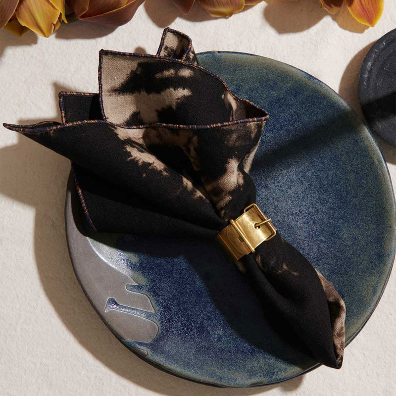 A black tie dye napkin is held by a gold napkin ring. The napkin is set on a blue glazed plate. The rest of the table setting features a neutral linen table cloth while orange flowers peek from the very top of the frame.