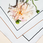 Here, all four off-white napkins are neatly splayed, unfolded, atop one another. We can see all 4 differently colored embroidered edges, including umber, sand, evergreen and navy. A large pink flower lays across the set.