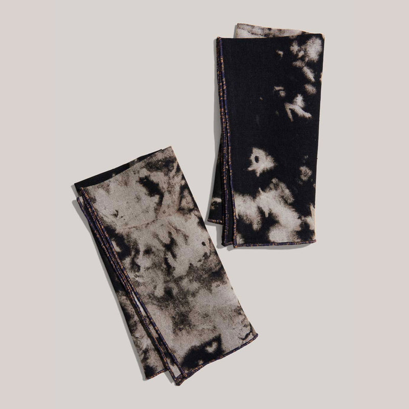 Two napkins are alone in this image. Each napkin measures 17 inches by 17 inches and are folded in half. The napkins are grey and black tie dye, feature a dark purple trim, and are sustainably made from dead stock fabric.