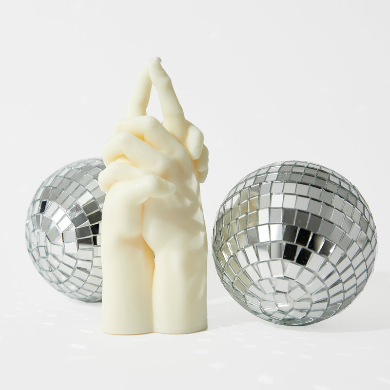 A white candle sits in the middle of this white frame--with two small disco balls measuring 3-5 inches in circumference around the candles. The white candle is made from two clasped hands, with the pointer finger of both hands pressed together. A white sustainably made candle sits at about 6-7 inches tall.