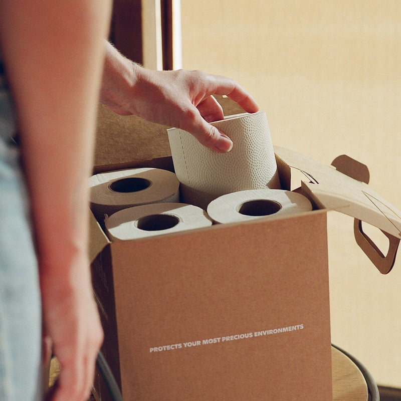 "A warm and textured photo that calls to mind sustainability. The photo peers from behind a figure. In the foreground and out of focus is a figure's jean-adorned leg and arm resting alongside. That same figure extends a hand out, pulling a roll of texture toilet paper from a brown box. The box contains four rolls and reads ""Protects Your Most Precious Environments."""
