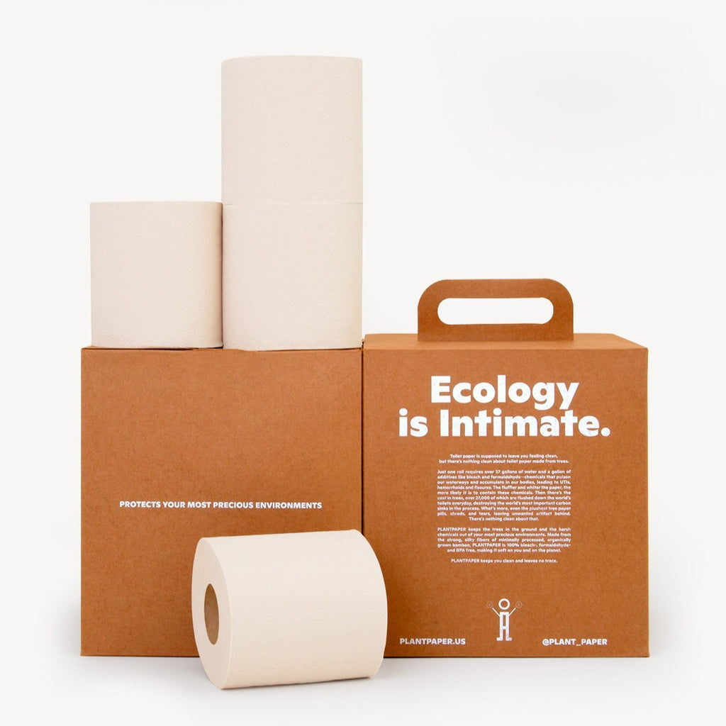 This image puts the Plantpaper's eco-friendly brand commitment front and center. Two warm brown boxes sit next to each other in front of a white background. The left box has three rolls of toilet paper stacked on top of it. In front of the boxes, a roll sits lazily on its side.