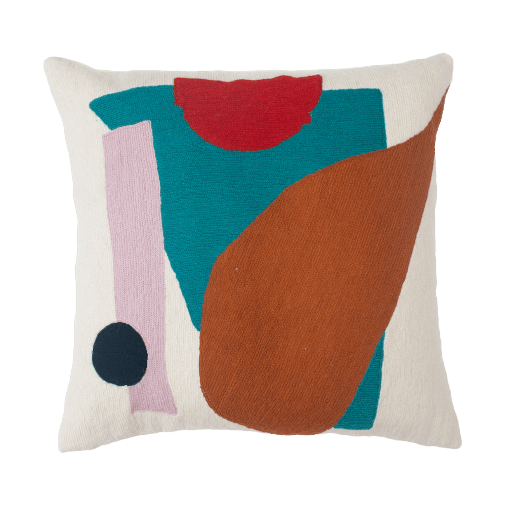 This is a sustainable pillow made of natural fibers and hand embroidered with wool thread by artisans in Kashmir, India. The white pillow has a geometric teal rhombus with a red half moon, blush stripe, black or navy dot and mustard and ochre colored tear drop emblazoned on top.