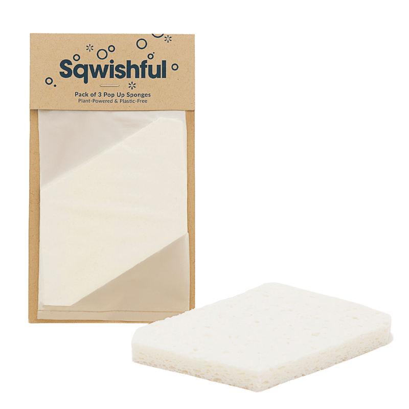 A white-colored sponge lays in the foreground of a white backdrop; it is sustainable, plastic-free, 100% plant-based and made from natural wood pulp. It is absorbent and fully expanded after having been exposed to water. To the left, the sponge is pictured in recyclable brown paper packaging. The sponge arrives dry, flat, and compressed which is convenient and space-saving (and also means a lower shipping carbon footprint!). It is biodegradable and beautiful in its simplicity.