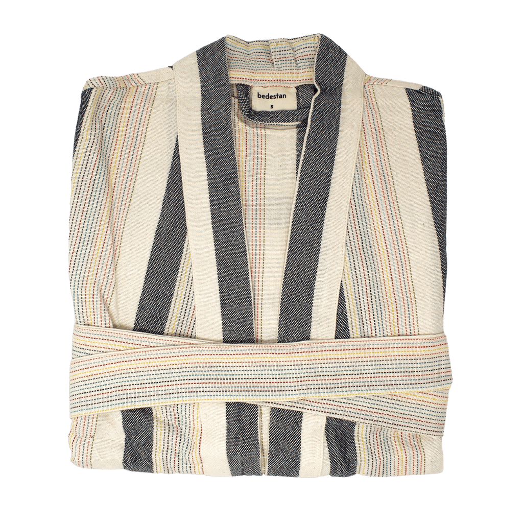 A robe is folded in half--with a tag displaying the brand name Bedestan. The robe has a rainbow striped belt wrapped around it. The robe itself features thick grey stripes and thinner rainbow stripes--all colored using veggie based dyes and loomed using traditional Turkish techniques.