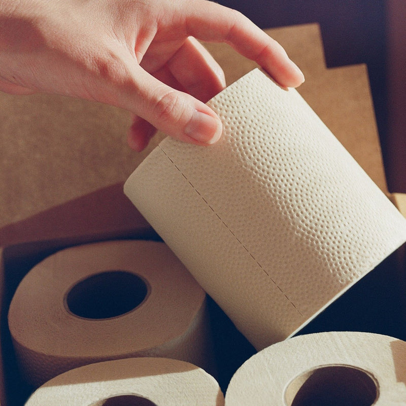 A close shot of a clean, un-manicured hand pulling a toilet paper roll from a box of four rolls. The lighting in this warm photo highlights the roll's texture, reminding you that it is a sustainable choice.
