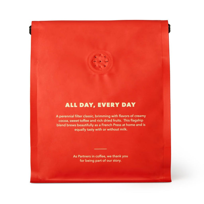 The back view of the same bright cherry red coffee bag--with a few perforations to let the beans aerate. A slogan splashed across the back in cream writing reads 'all day, every day'. Also included is a cute note, thanking you being part of their story! No Partner's, it's our story now.