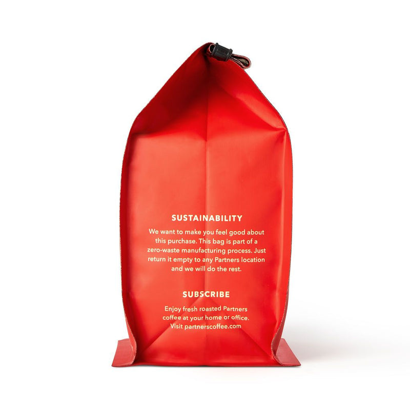 The other side view of the bright red coffee bag with a message about sustainability and an offer for a subscription service. Easy peasy lemon...coffee.