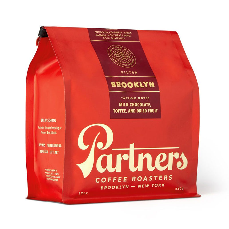 A bright, cherry red bag of coffee sits at a 45 degree angle in the center of a plain white background. Across the front in cream, 60's style lettering lists the brand name 'Partners coffee roasters, brooklyn, ny'. The small parcel is sealed with a burgundy sticker at the top which lists the tasting notes to be milk chocolate, toffee and dried fruit.