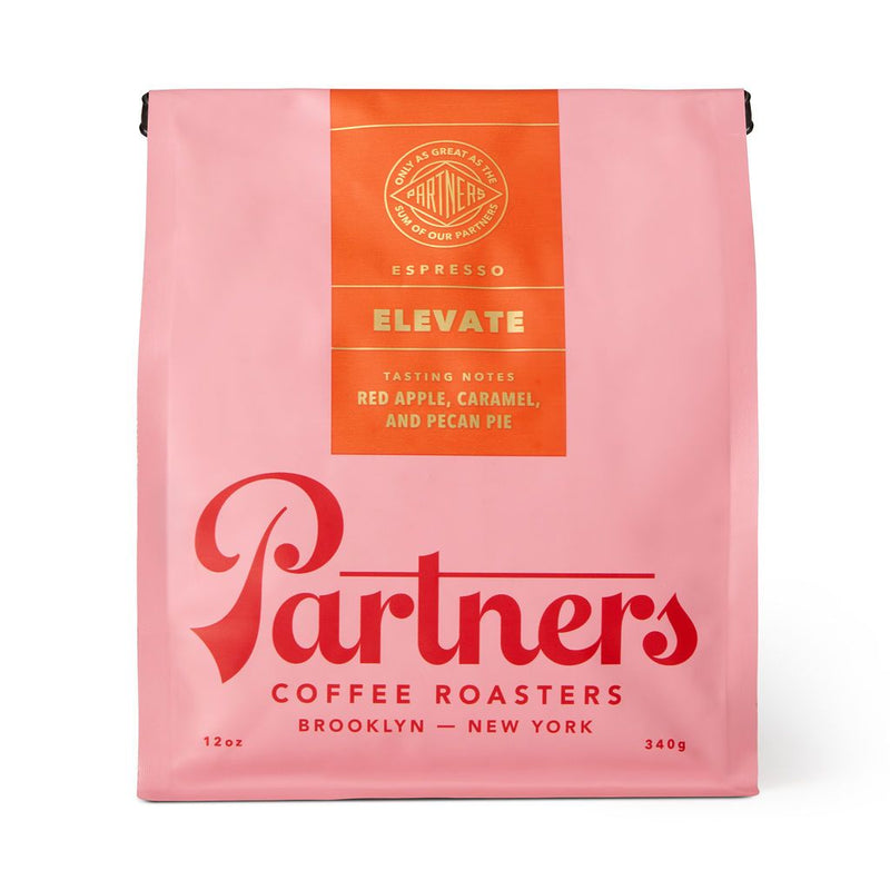 You love coffee, you love fall, you love cozy and cute things. You're going to love this pastel pink bag of Partners ELEVATE coffee. PARTNERS is emblazoned across the front in cherry red font, and tasting notes listed on the sealing orange top label include fall's best red apple, caramel and...would you believe...pecan pie! In one cup! The possibilities are endless!