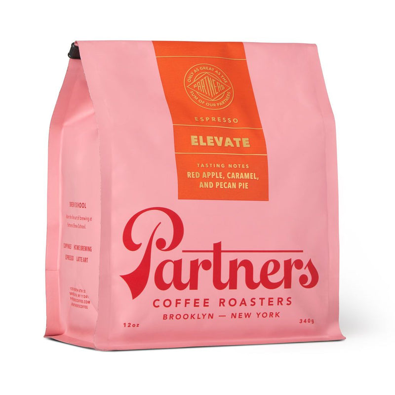 You love products photographed on 45 degree angles, coffee, you love fall, you love cozy and cute things. You're going to love this pastel pink bag of Partners ELEVATE coffee. PARTNERS is emblazoned across the front in cherry red font, and tasting notes listed on the sealing orange top label include fall's best red apple, caramel and...would you believe...pecan pie! In one cup! The possibilities are endless!