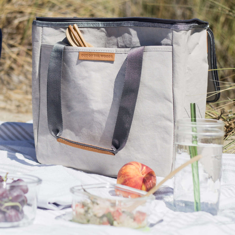 A light grey rectangular cooler bag (made sustainably out of paper!) sits large in the middle of the frame on a beach blanket with grasses blurry in the background. In the large front pocket, bamboo eating utensils poke out. In the foreground is a peach, water in a large mason jar with glass straw, and two clear containers with pasta salad and grapes. It is a perfect beach picnic lunch scene--light, bright, airy, and sustainably-minded!