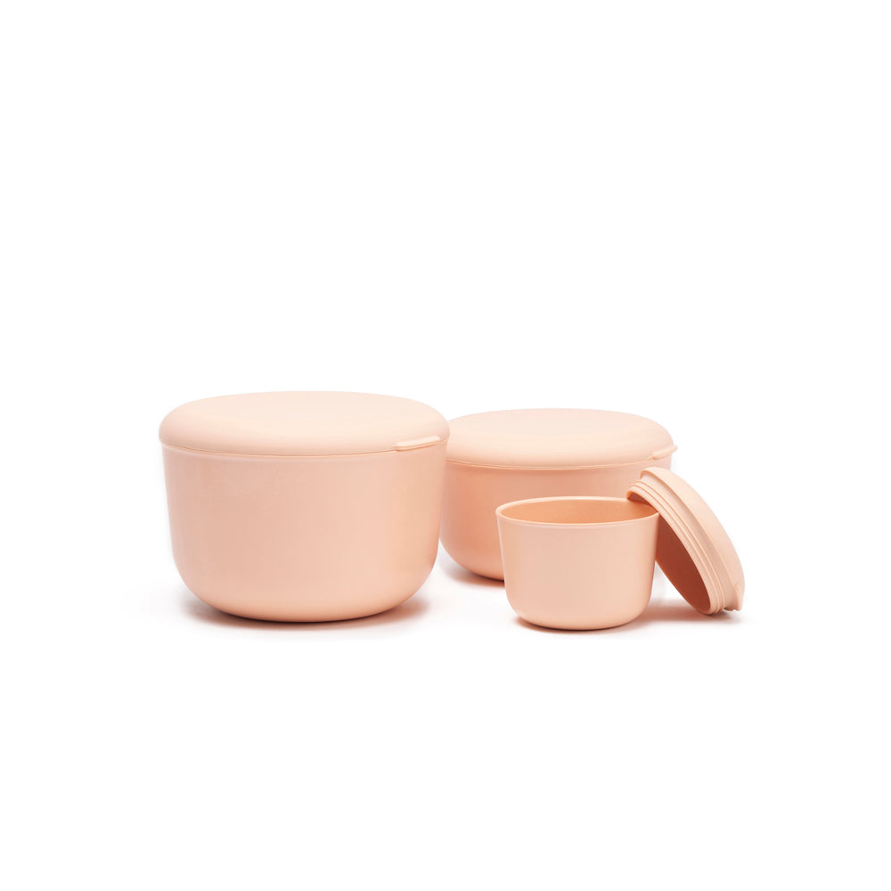 Three bamboo storage containers are arranged on the white background. There is a large blush container, that is sealed, and you can see its depth and how the top seals very well. In the background is the medium size, also sealed, and the smallest size is in front, with the lid leaning up against it. The way the lid is styled, you can see that it's a screw top to-go container with a soft top, perfect for children's snacking or packing a lunch to work or school.