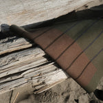 A woman in a sustainable, ecru waffle knit robe is drying her damp hair with a waffle knit towel made of the same sustainable and eco-friendly organic bamboo material.  She is barefoot, legs casually crossed, with the robe cuffed just above the wrists. The robe hits a few inches above her ankle, and is oversized and unisex. The rest of the room is well decorated with grey bamboo lyocell sustainable bedding and a mod white column nightstand table.