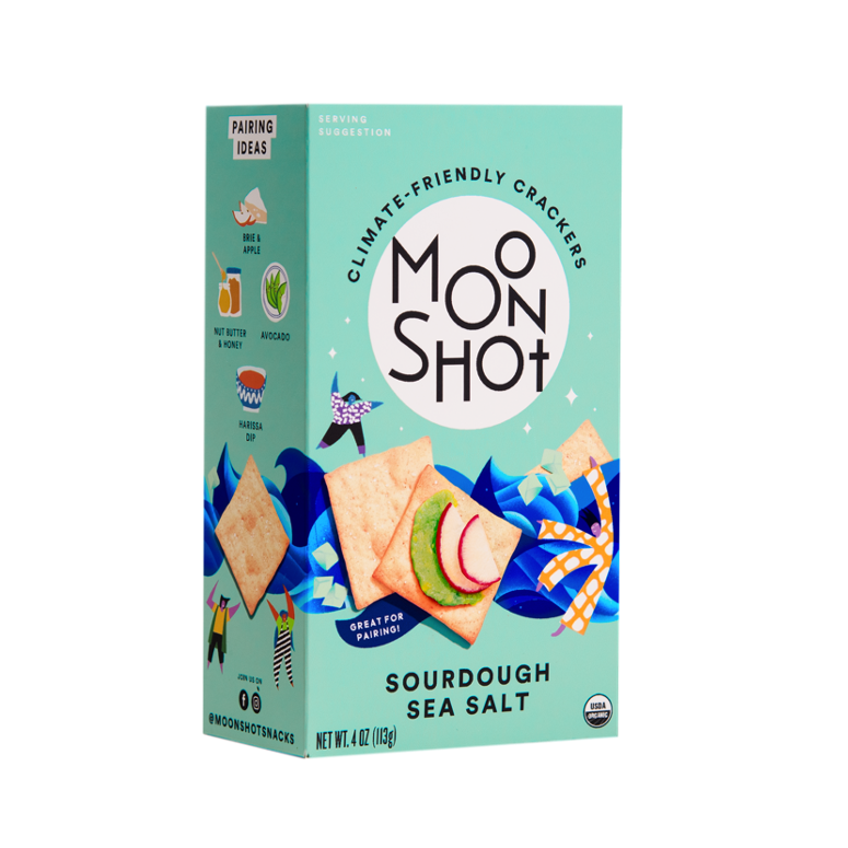 This is an image of Moonshot climate friendly crackers. The sourdough sea salt variation box is light blue in color and includes Moonshot's black and white logo, an image of two crackers with toppings, and illustrations of women dancing and dark blue ocean waves.