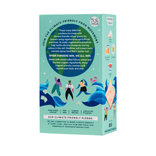 This is the back of Moonshot's Sourdough sea salt cracker box. It features a green and blue illustration of the world with written information over the illustration about their regenerative agriculture practices. An illustration of three women dancing and dark blue waves sits below the world. Finally, Moonshot's climate-friendly pledge is found at the bottom of the box.