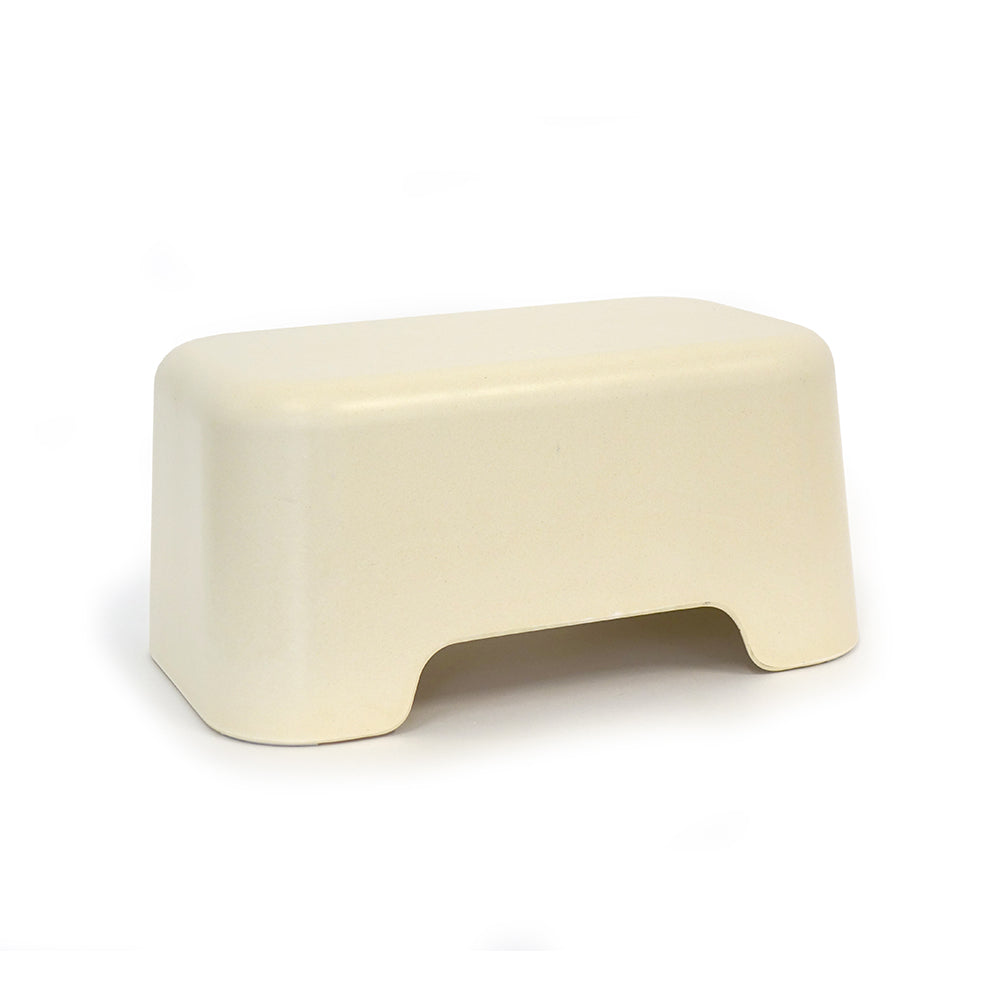 A white bamboo step stool for children sits on a white background. It is about a foot high and the perfect size for kids.