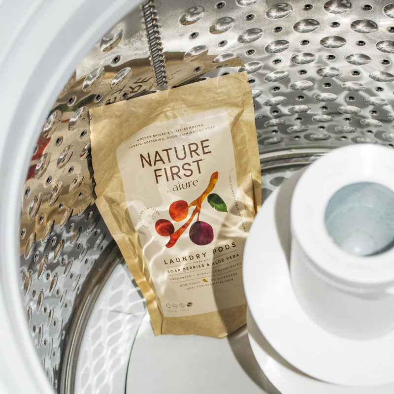 The kraft paper bag of biodegradable laundry pods sits inside of on empty washing machine barrel