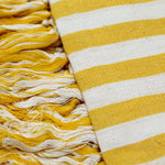 A close up shot of the Patara Pestemal--or Turkish Towel--shows alternating white and yellow stripes and tassels made from single threads of yellow and white yarn. The towel is woven in a family atelier in Turkey, dries quickly, and is very absorbent.