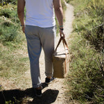 A man in a white shirt and grey pants walks down a small dirt path with grasses on both sides of him. He is shown from behind, walking and holding a brown cooler tote bag. The bag is made from paper and sustainable and keeping his picnic snacks cold! It is also a perfect and stylish accompaniment to his outfit.