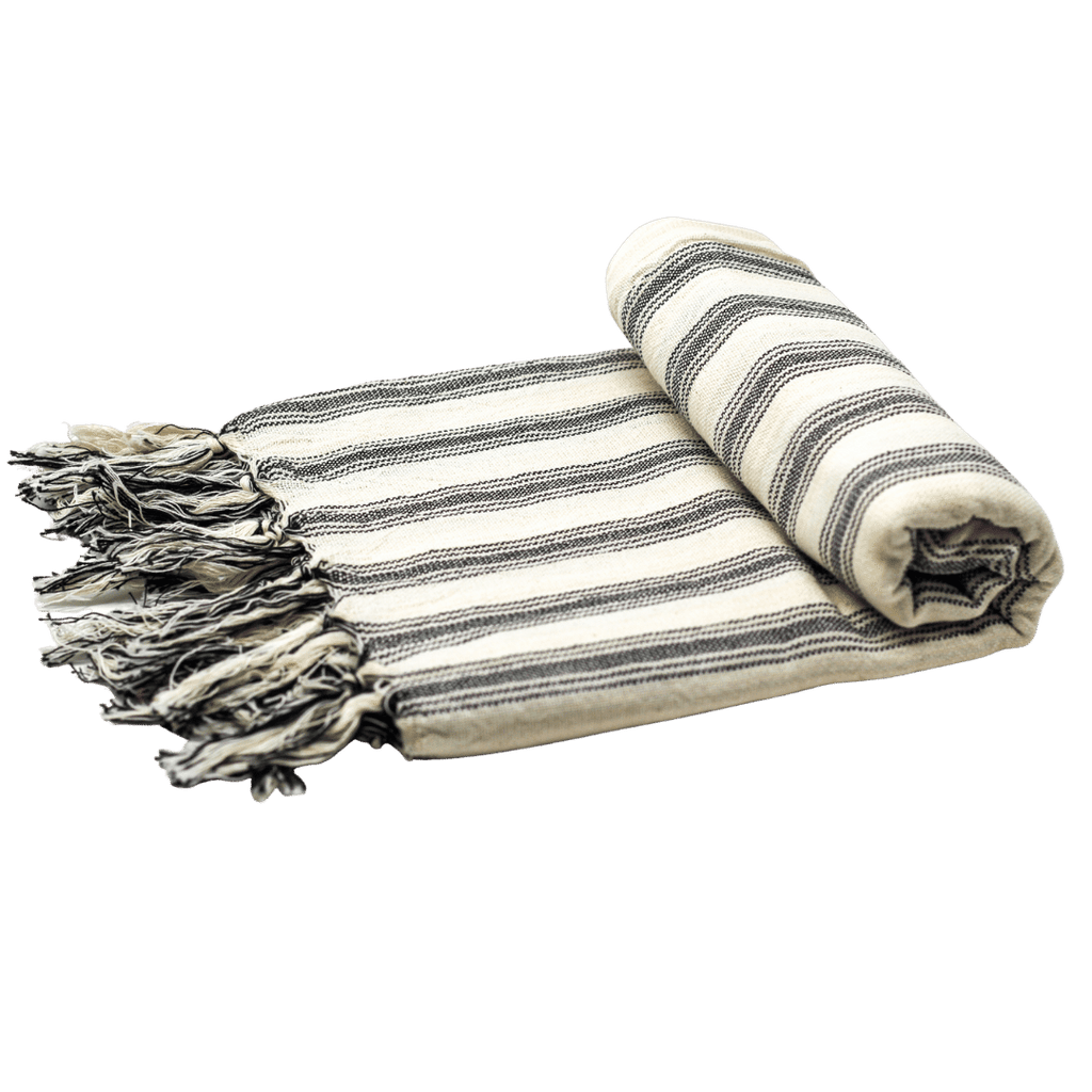 "A turkish towel with tassels on its edge is half rolled-up from its left side. The towel has black and white stripes, is made from 100% linen and cotton, and measures 78.7"" x 39.3"". Loomed using traditional techniques in a small-family run atelier in Turkey, the towels are also colored using natural, veggie-based dyes."
