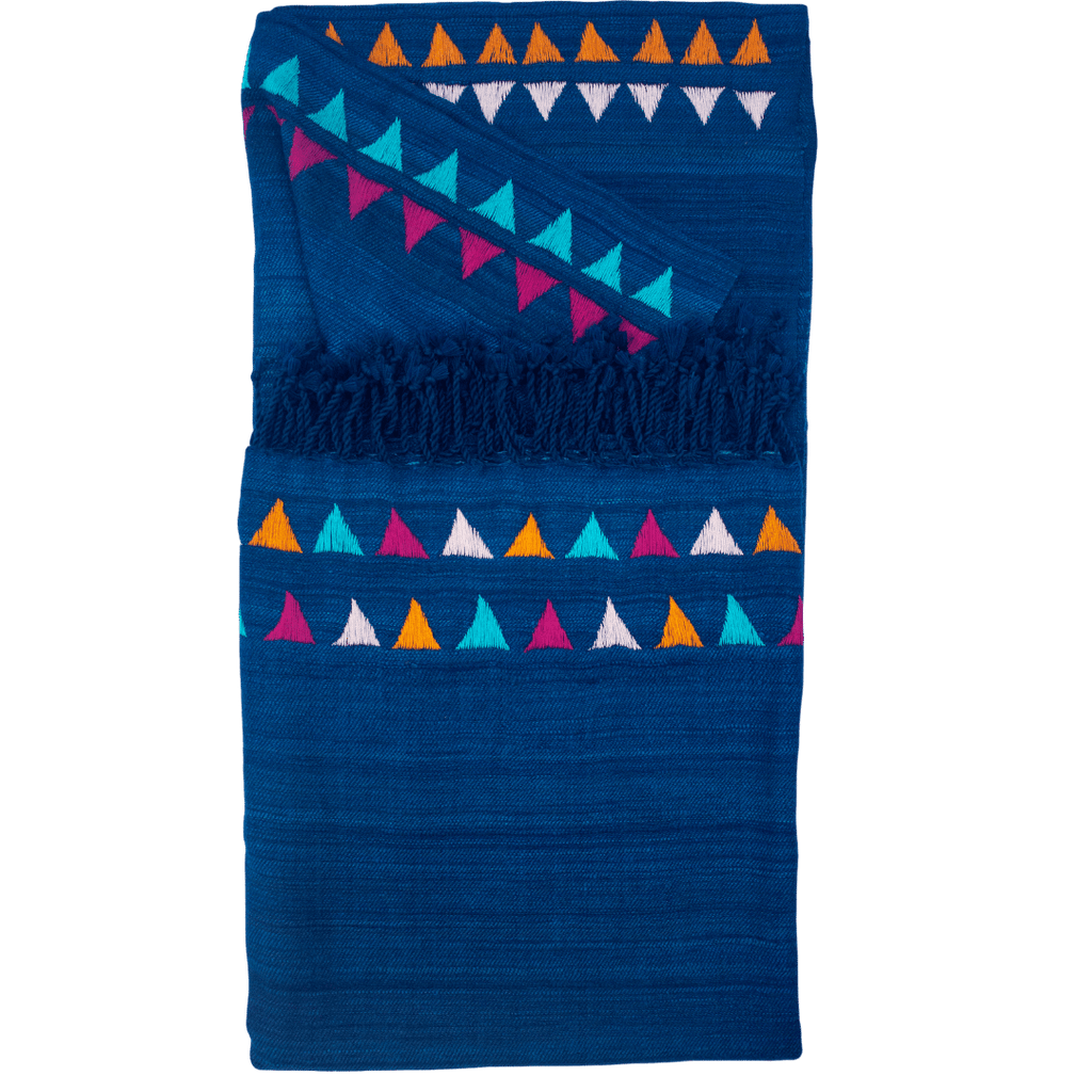 This is a multicolored indigo throw blanket that is sized for use on the couch. It is handwoven from indigo blue silk and wool and then embroidered by hand with cotton threads in bright hues like magenta, pink, yellow and lilac. There is a bit of fringe below the embroidery.