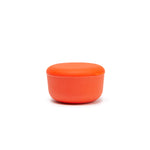 Coral or persimmon colored medium sized food storage container made of sustainable bamboo stands alone in front of a white background.