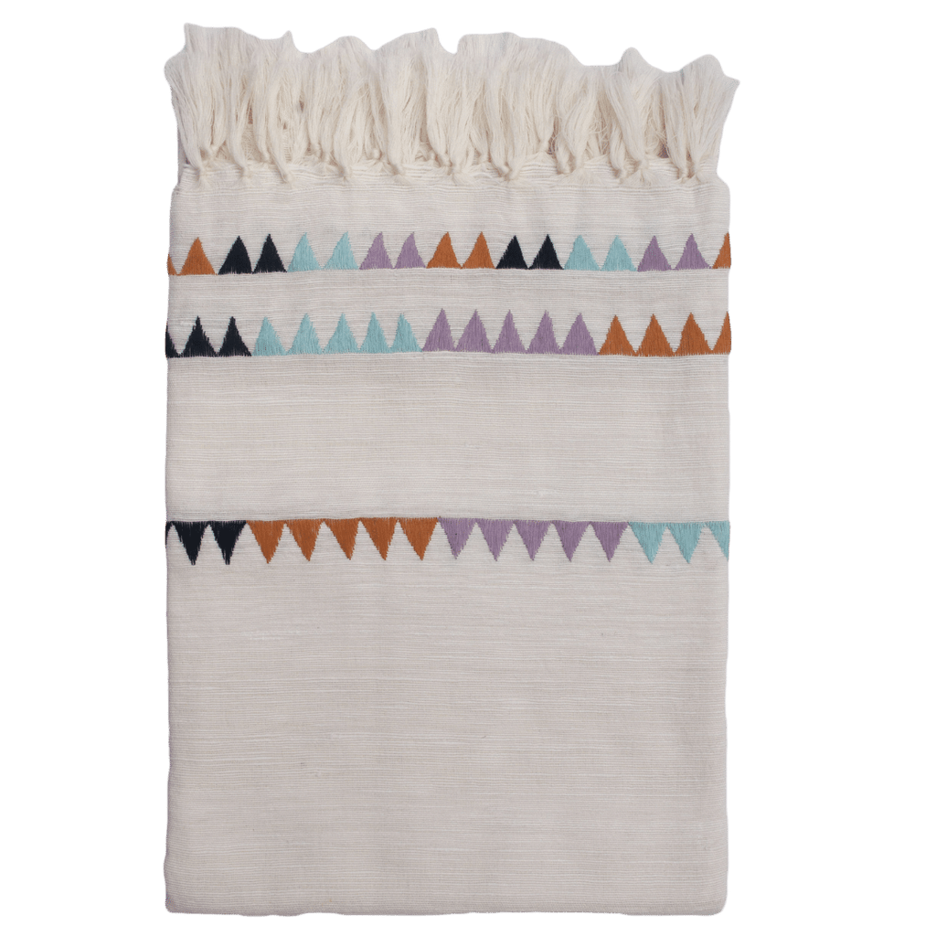 This sustainable throw blanket is cream colored with a hand embroidered design of mustard, lilac, sea foam blue and cobalt, with a hand knotted fringe.