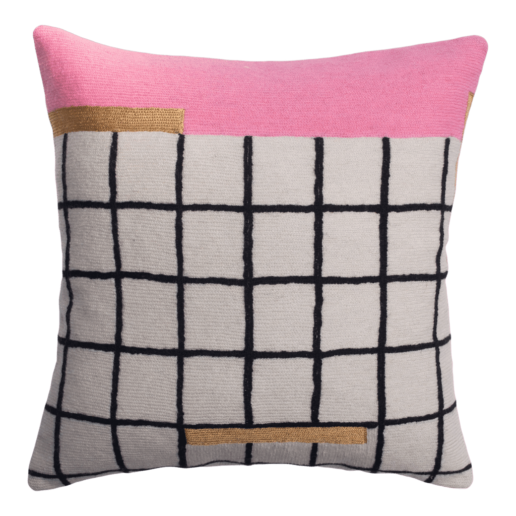 This is a sustainable throw pillow with a bright and bold pattern, complete with a white and black grid pattern, a pink stripe and gold accents.