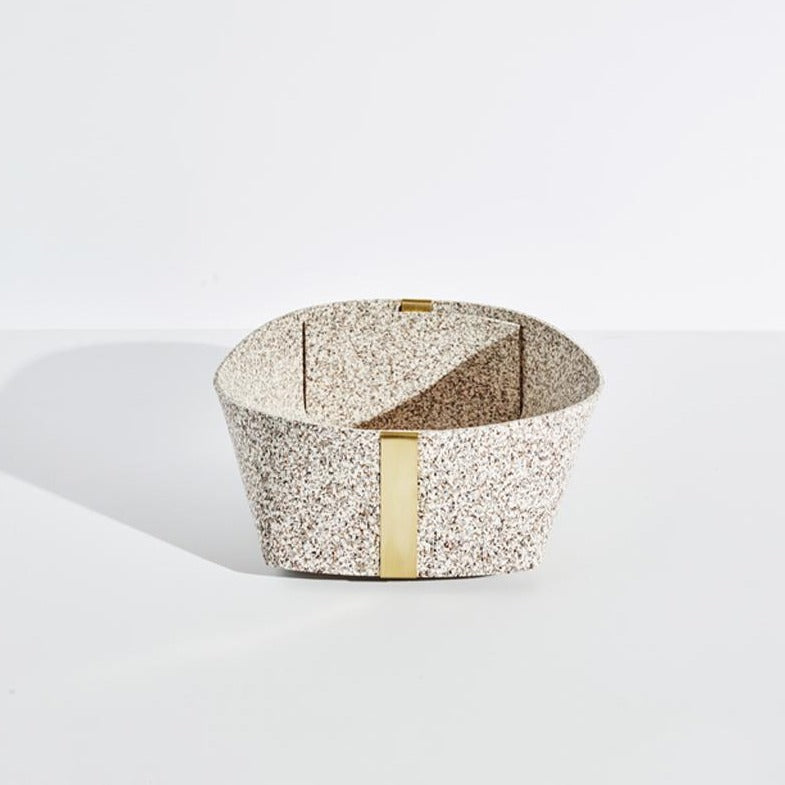 The large sand speckled basket with gold accents sits on a plain white background.