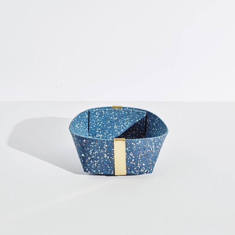 The medium blue speckled basket with gold accents sits on a plain white background.