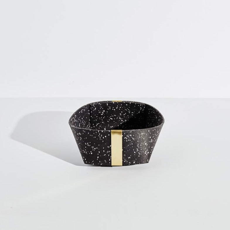 The medium black and white speckled basket with gold tabs sits in the middle of a plain white background. She looks sturdy, and ready to hold your paperclips, pocket notebooks, hopes and dreams.
